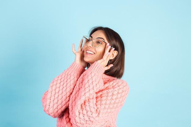 Młoda Brunetka W Różowym Swetrze Na Białym Tle Na Niebieskiej ścianie Darmowe Zdjęcia