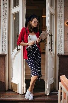 Młoda brunetka w stylu paryskim, w spódnicy w kropki, białej bluzce, koszuli, berecie i trampkach, z aparatem na ramieniu, pozuje na tle jasnej ściany budynku, patrząc na mapę