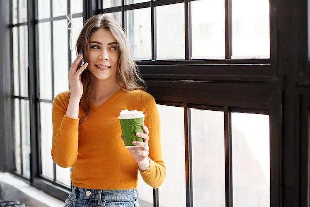Młoda brunetka w żółtym swetrze stoi przy oknie z filiżanką kawy i telefonem w dłoni i rozmawia przez telefon