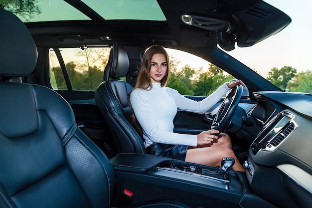 Młoda brunetka z długimi włosami w białym swetrze i czarnej skórzanej spódnicy z pięknymi nogami prowadząca drogi samochód