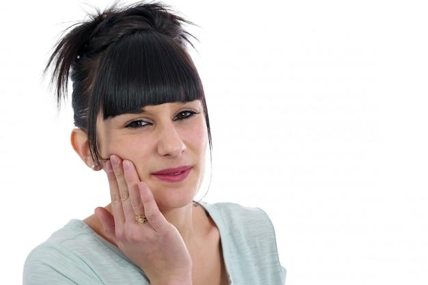 Młoda brunetka z toothache na bielu ,.