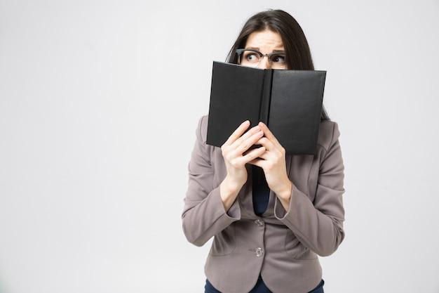 Młoda brunetka zakryła podłogę jej twarzy dziennikiem na białym