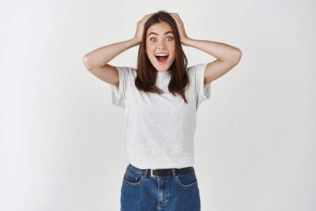 Młoda brunetka, zdziwiona z przodu, krzyk radości i podniecenia, trzymająca się za głowę z niedowierzania, stojąca nad białą ścianą