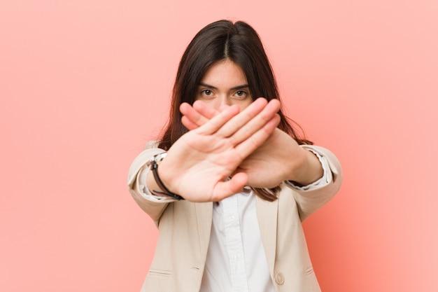 Młoda brunetki biznesowa kobieta przeciw menchii robi zaprzeczenie gestowi