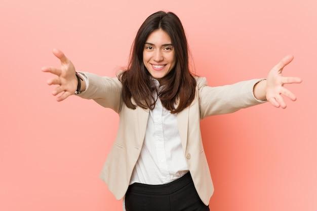 Młoda brunetki biznesowa kobieta przeciw różowej ścianie czuje się pewnie, ściskając aparat.