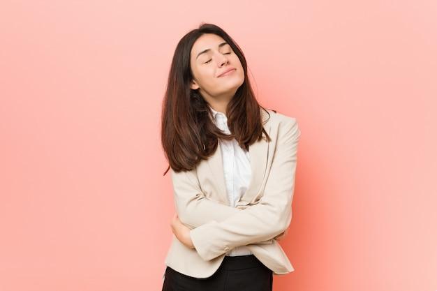 Młoda brunetki biznesowa kobieta przeciw różowej ścianie ściska, ono uśmiecha się beztroski i szczęśliwy.