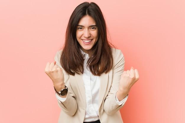 Młoda brunetki biznesowa kobieta przeciw różowemu tłu dopinguje beztroskiego i podekscytowanego.