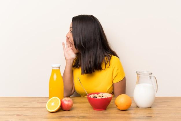 Młoda brunetki dziewczyna ma śniadania mleko krzyczy z usta szeroko otwarty