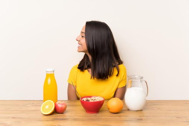 Młoda brunetki dziewczyna ma śniadania mleko patrzeje strona