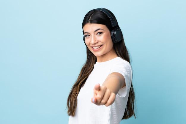 Młoda brunetki dziewczyna nad błękit ściany ścianą słucha muzykę i wskazuje przód