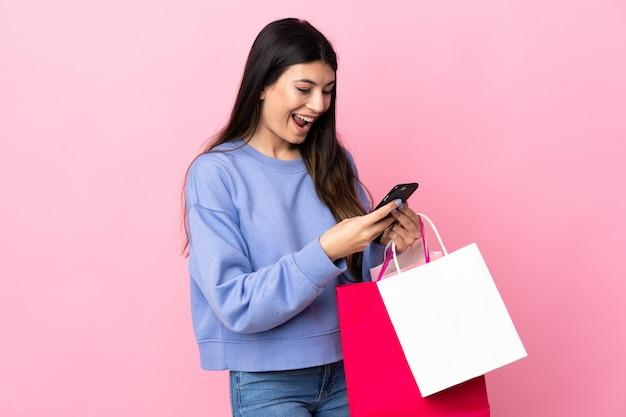 Młoda brunetki dziewczyna nad menchii ściany mienia torba na zakupy i pisać wiadomości z jej telefonem komórkowym przyjaciel