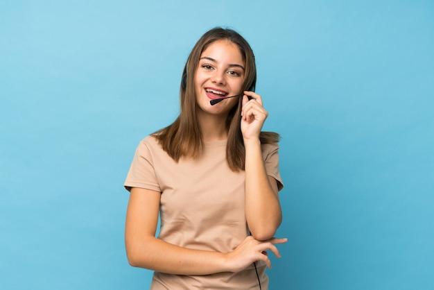 Młoda brunetki dziewczyna nad odosobnioną błękit ścianą pracuje z słuchawki