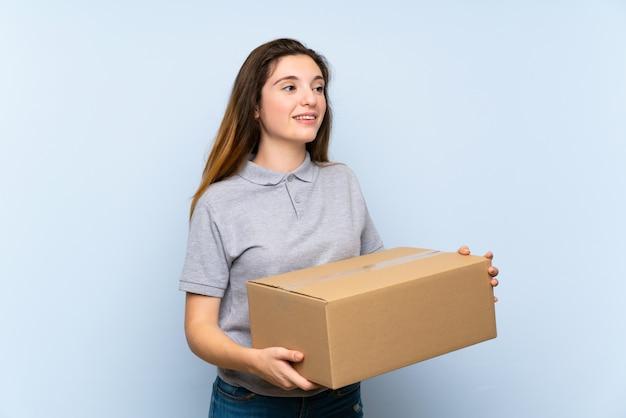 Młoda brunetki dziewczyna nad odosobnioną błękit ścianą trzyma pudełko, aby przenieść go do innego miejsca