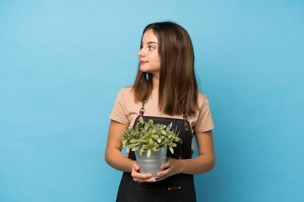 Młoda brunetki dziewczyna nad odosobnionym błękitem bierze flowerpot