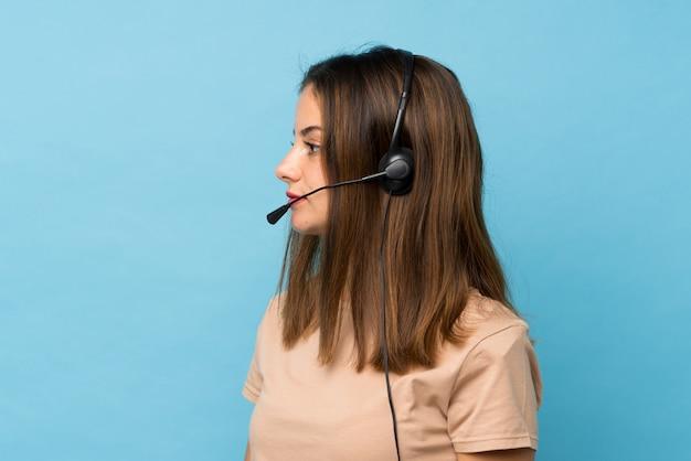 Młoda brunetki dziewczyna nad odosobnionym błękitnym działaniem z słuchawki