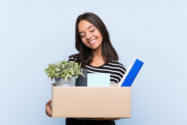 Młoda brunetki dziewczyna robi ruchowi podczas gdy podnoszący pudełko pudełko rzeczy z szczęśliwym wyrażeniem