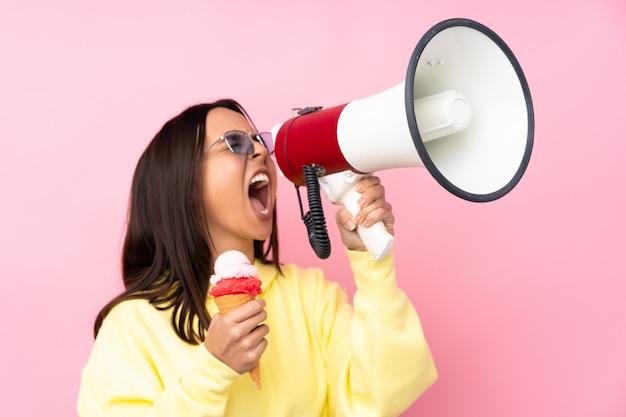 Młoda brunetki dziewczyna trzyma kornet lody nad odosobnioną menchii ścianą krzyczy przez megafonu