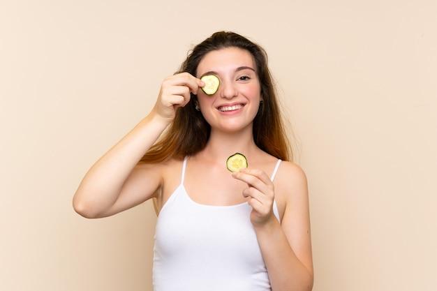 Młoda brunetki dziewczyna trzyma plasterki ogórek