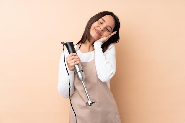 Młoda brunetki dziewczyna używa ręki blender nad odosobnioną ścianą robi sen gestowi w dorable wyrażeniu