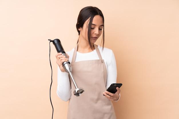Młoda brunetki dziewczyna używa ręki blender nad odosobnioną ścienną mienie kawą brać daleko od i wiszącą ozdobą