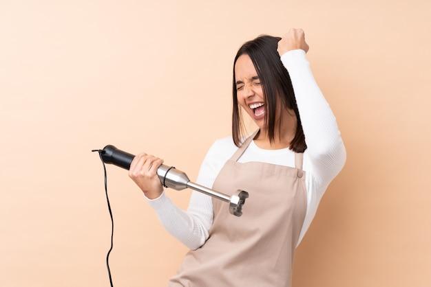 Młoda brunetki dziewczyna używa ręki blender świętuje zwycięstwo nad odosobnioną ścianą