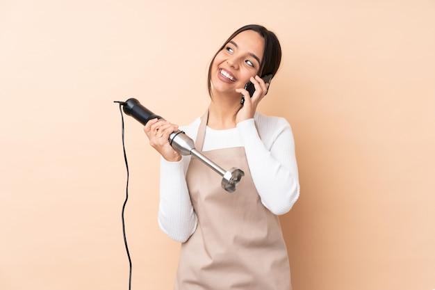 Młoda brunetki dziewczyna używa ręki blender trzyma kawę brać daleko od i wiszącą ozdobę