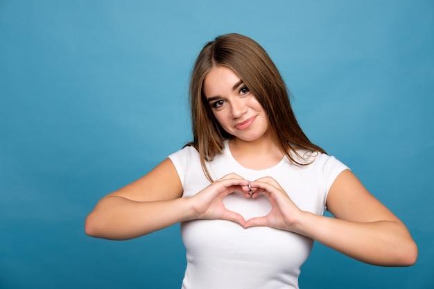 Młoda brunetki dziewczyna w białym koszulki seansie słucha szyldowego używa ręki, błękitny tło