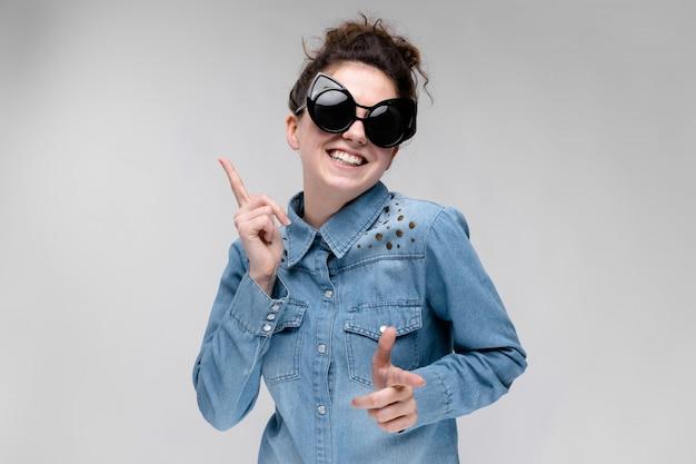 Młoda brunetki dziewczyna w czarnych szkłach. okulary dla kota włosy są zebrane w kok. dziewczyna tańczy