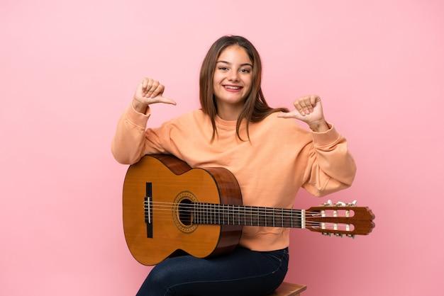 Młoda brunetki dziewczyna z gitarą nad odosobnionym różowym dumnym i zadowolonym z siebie