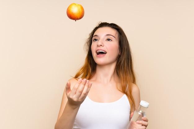 Młoda brunetki dziewczyna z jabłkiem i butelką wody
