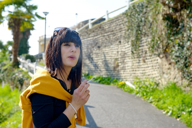 Młoda brunetki kobieta dymi papierosowego outside