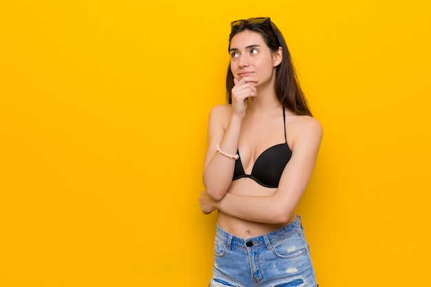 Młoda brunetki kobieta jest ubranym bikini patrzeje z ukosa z wątpliwym i sceptycznym wyrażeniem