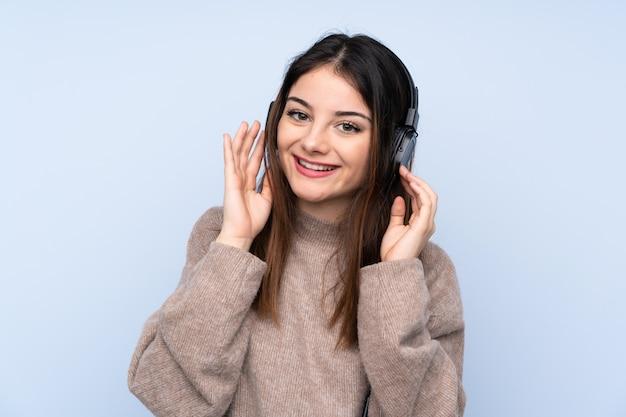 Młoda brunetki kobieta nad błękit ściany ścianą słuchającą muzykę