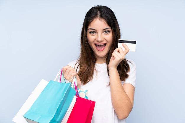Młoda brunetki kobieta nad błękit ściany ścianą trzyma torba na zakupy i zaskakująca