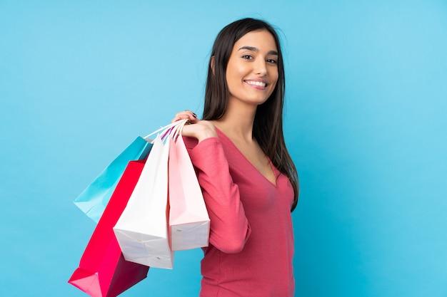 Młoda brunetki kobieta nad błękitnymi mień torba na zakupy i ono uśmiecha się