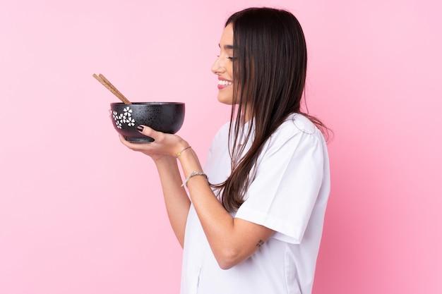Młoda brunetki kobieta nad menchiami trzyma puchar kluski z pałeczkami