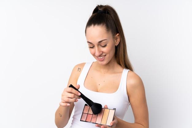 Młoda brunetki kobieta nad odosobnioną biel ścianą z makeup paletą