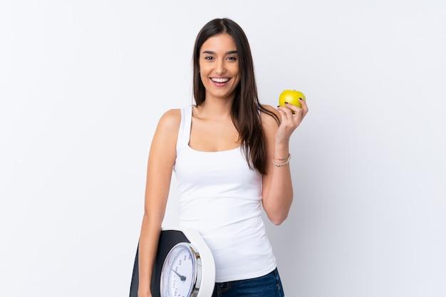 Młoda brunetki kobieta nad odosobnioną biel ścianą z ważyć maszynę z jabłkiem i