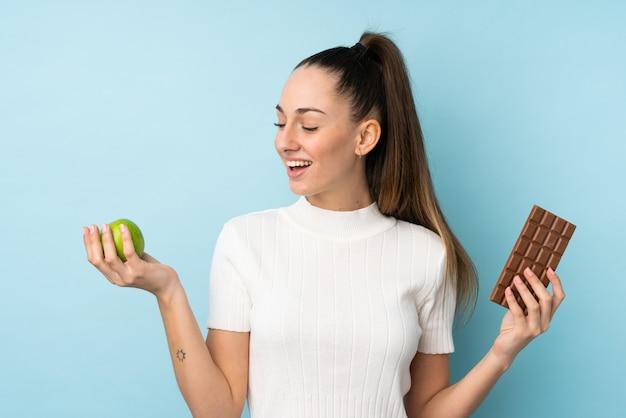 Młoda brunetki kobieta nad odosobnioną błękit ścianą bierze czekoladową pastylkę w jednej ręce i jabłko w drugiej