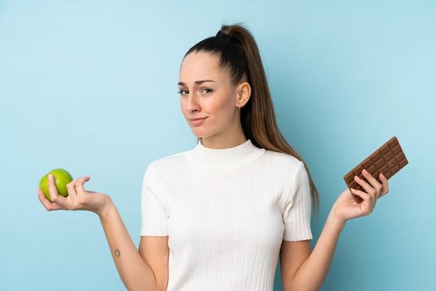 Młoda brunetki kobieta nad odosobnioną błękit ścianą ma wątpliwości podczas gdy brać czekoladową pastylkę w jeden ręce i jabłko w inny