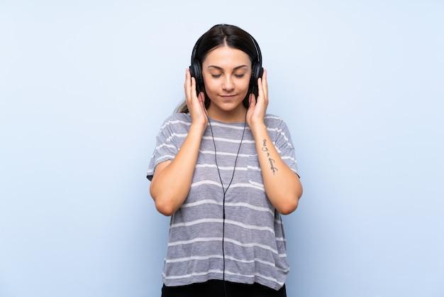 Młoda brunetki kobieta nad odosobnioną błękit ścianą słucha muzyka z hełmofonami