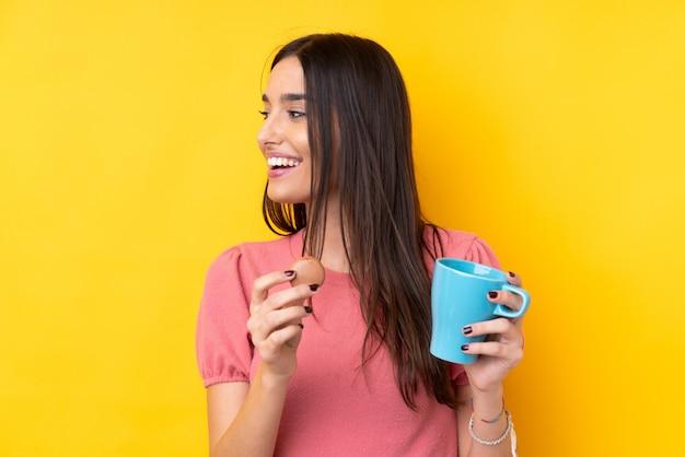 Młoda brunetki kobieta nad odosobnioną kolor żółty ścianą trzyma kolorowych francuskich macarons i filiżankę mleka