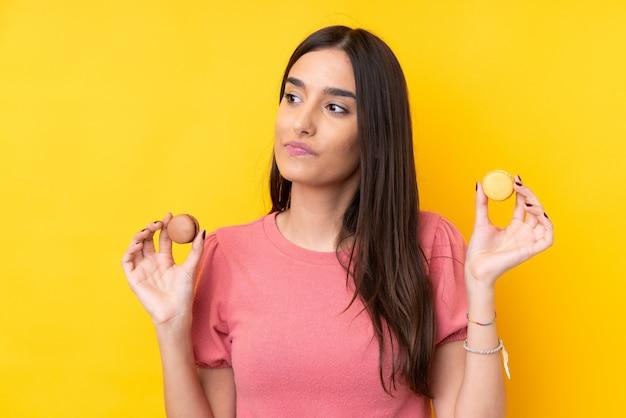 Młoda brunetki kobieta nad odosobnioną kolor żółty ścianą trzyma kolorowych francuskich macarons i główkowanie