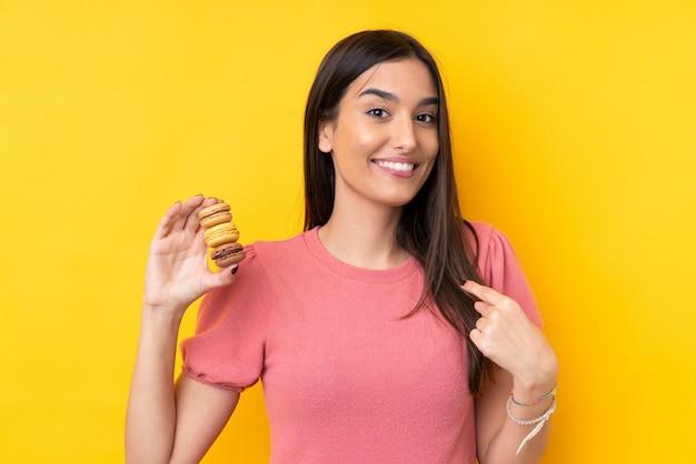 Młoda brunetki kobieta nad odosobnioną kolor żółty ścianą trzyma kolorowych francuskich macarons z niespodzianki wyrażeniem