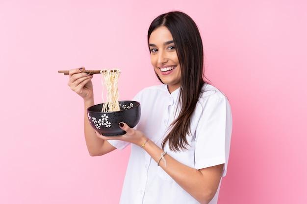 Młoda brunetki kobieta nad odosobnioną menchii ścianą trzyma puchar kluski z chopsticks