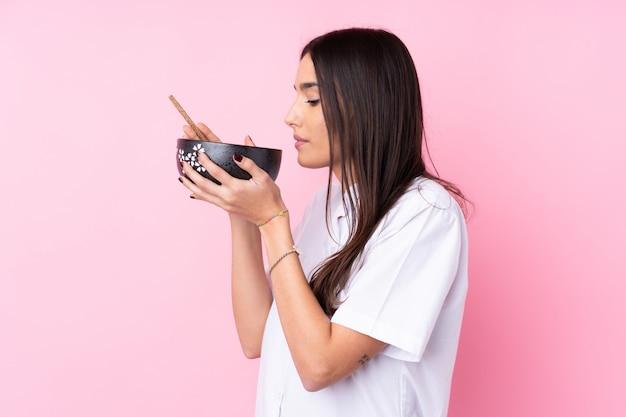 Młoda brunetki kobieta nad odosobnioną menchii ścianą trzyma puchar kluski z pałeczkami i je je
