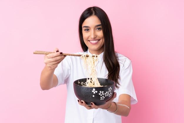 Młoda brunetki kobieta nad odosobnioną menchii ścianą trzyma puchar kluski z pałeczkami i oferuje je