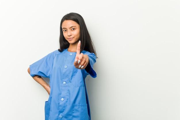 Młoda brunetki kobieta pokazuje liczbę jeden z palcem