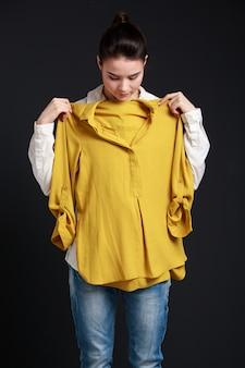 Młoda brunetki kobieta próbuje koszula dalej
