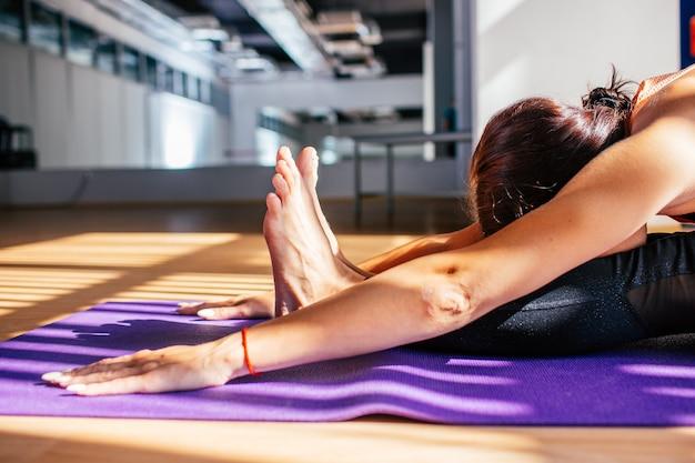 Młoda brunetki kobieta robi rozciąganiu ćwiczy w lekkim studiu. dobre samopoczucie, koncepcja odnowy biologicznej.